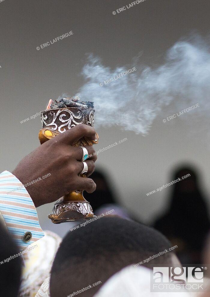 Stock Photo: Sunni muslim man spreading insence with a censer during the Maulidi festivities in the street, Lamu County, Lamu Town, Kenya.