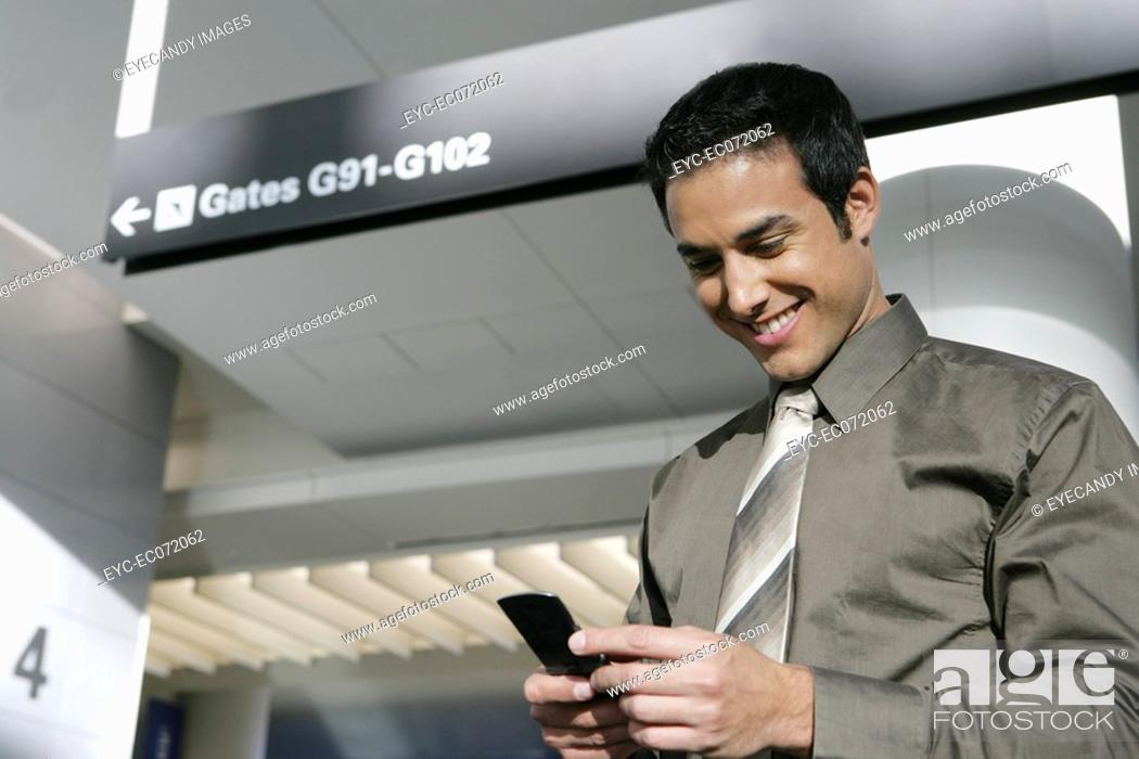 Stock Photo: Young businessman text messaging in airport.