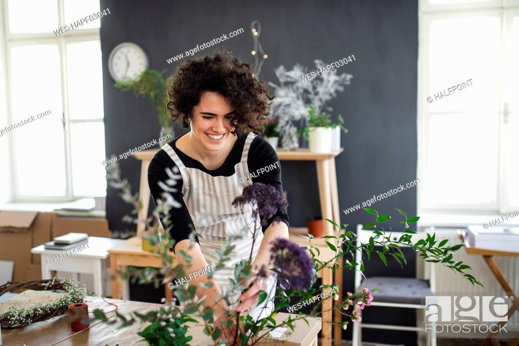 Stock Photo: Smiling young woman arranging flowers in a small shop.