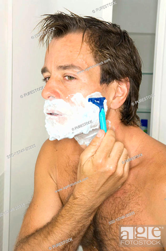 Stock Photo: Portrait of a young man shaving in the bathroom.