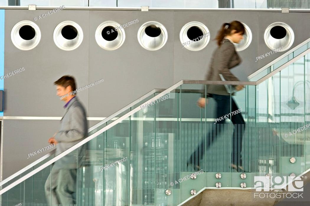 Stock Photo: Side profile of a businessman and a businesswoman walking on a staircase.