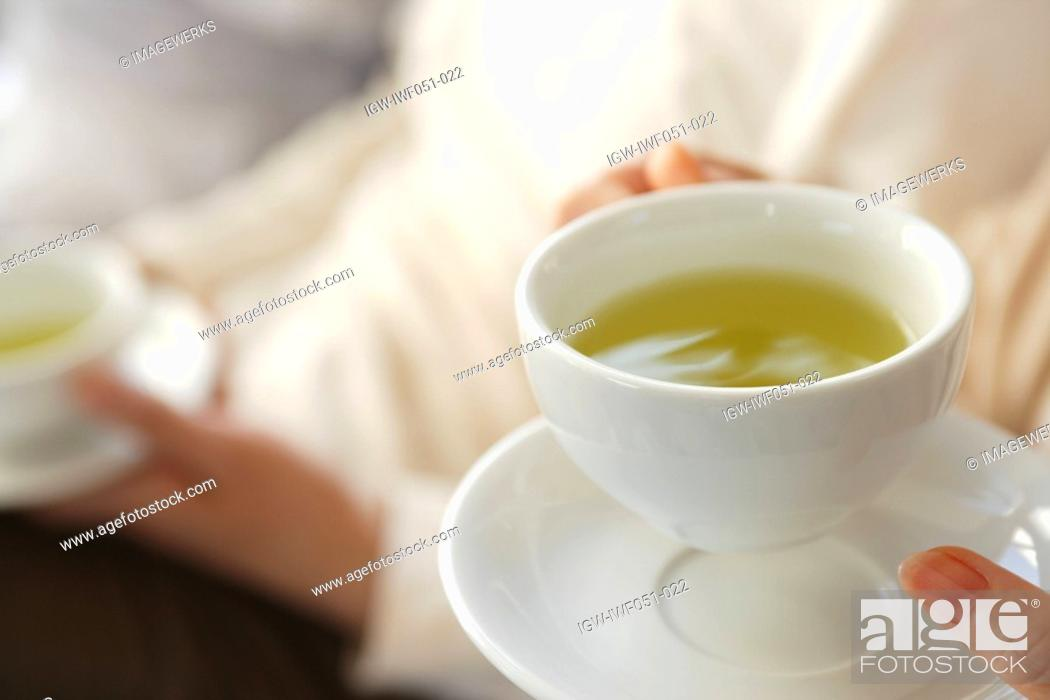 Stock Photo: Person holding cup of tea, close-up.
