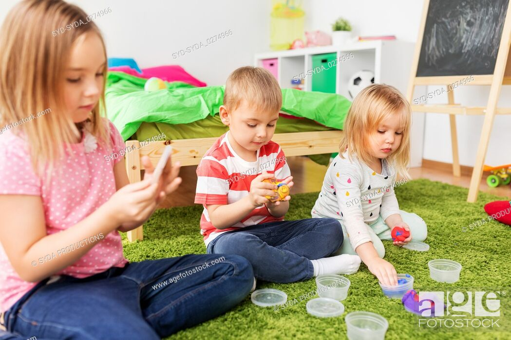 Stock Photo: children with modelling clay or slimes at home.