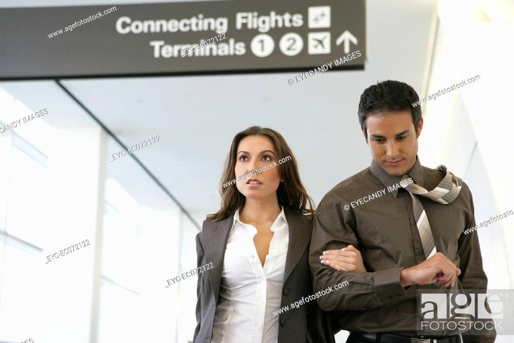 Stock Photo: Young business couple walking in airport.