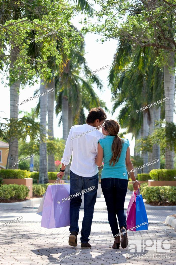 Stock Photo: A young couple walking arm in arm and carrying shopping bags.