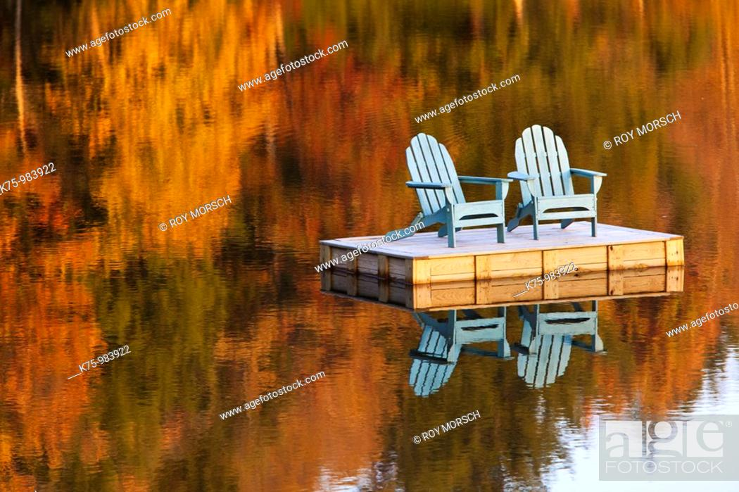 Stock Photo: two adirondack chairs on dock in autumn.