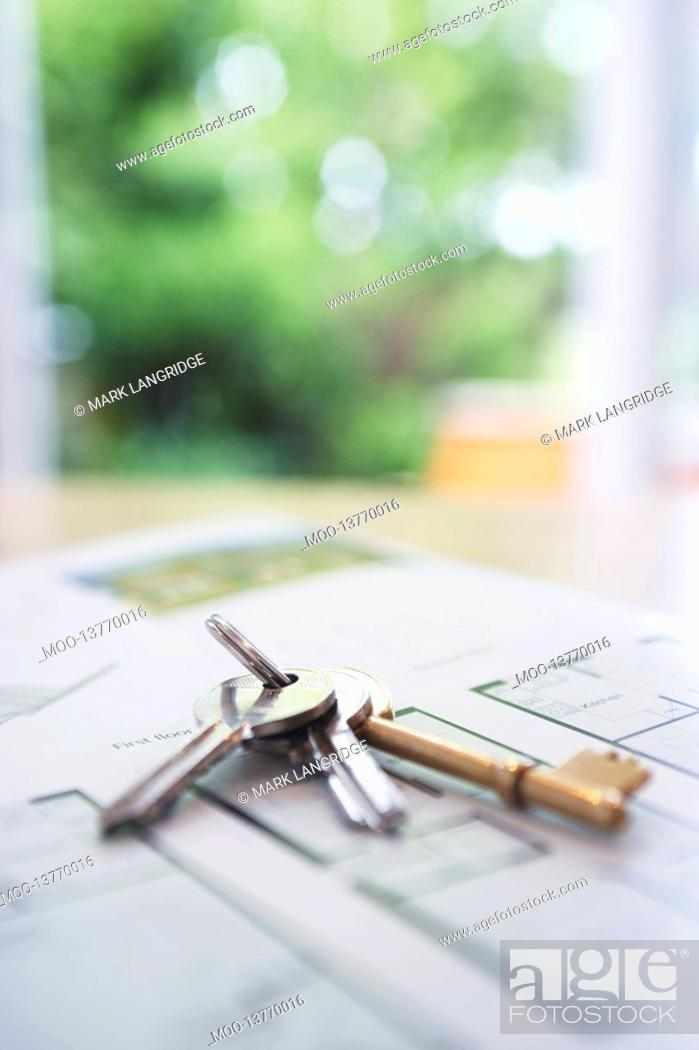 Stock Photo: Key ring with three keys lying on architectural blueprints close-up.