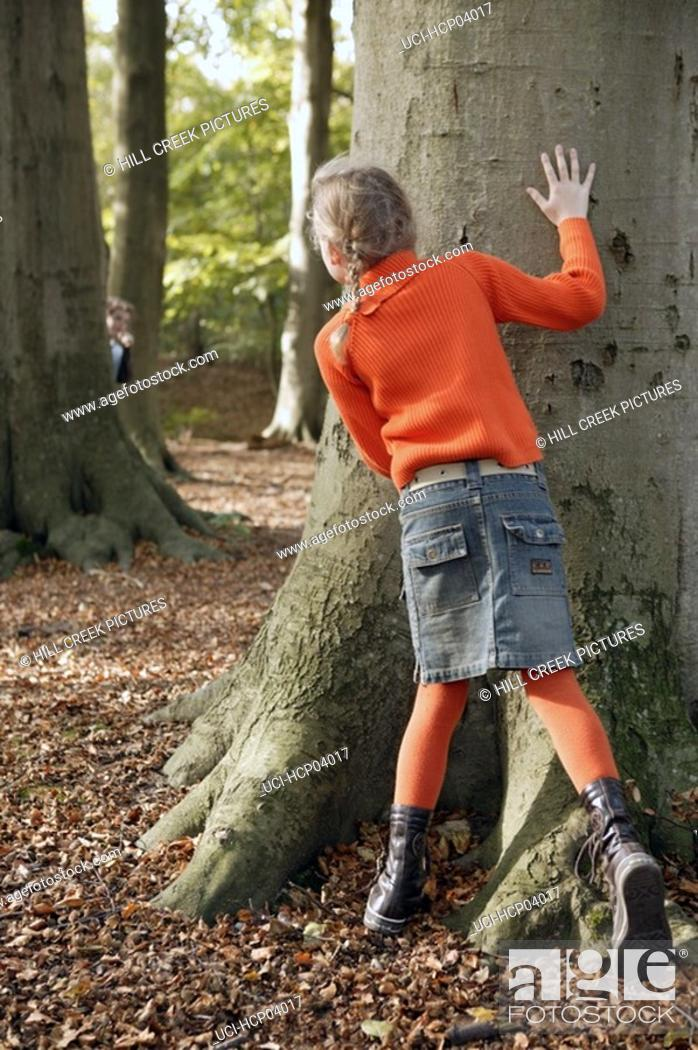 Stock Photo: Young girl playing hide and seek in forest.