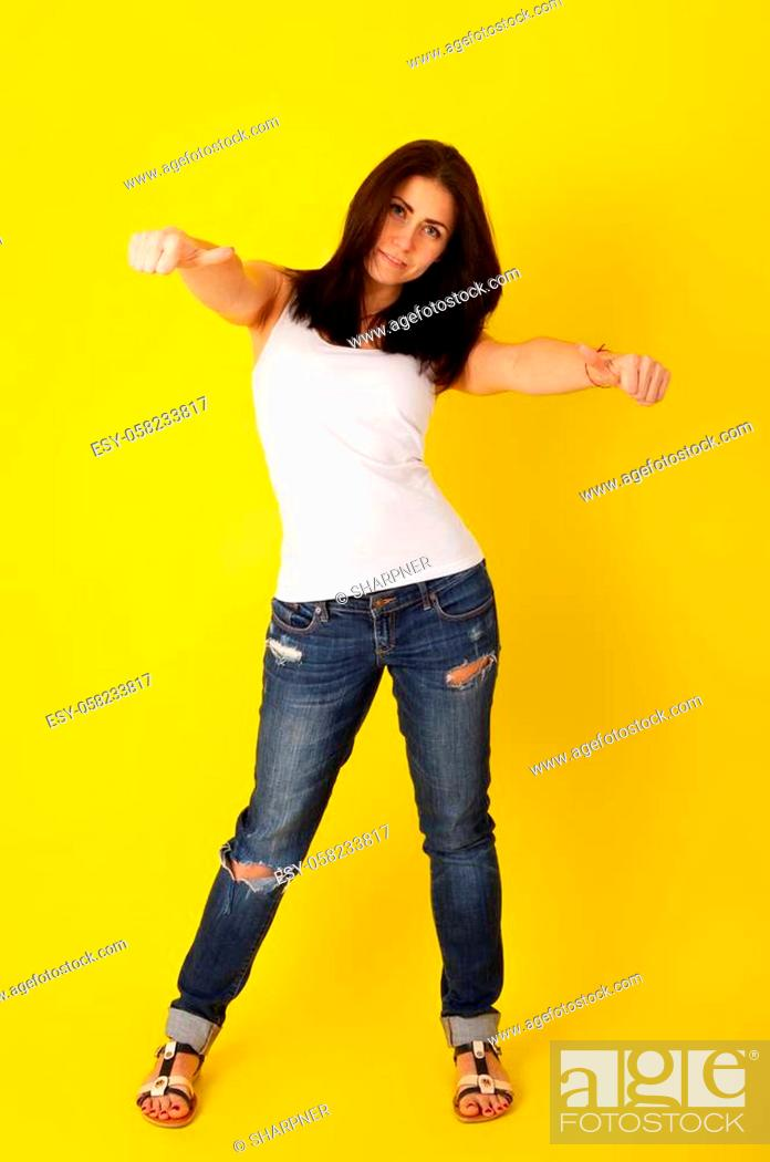 Stock Photo: Young cute girl in casual clothes shows a thumbs up in an approving gesture on a bright yellow background.