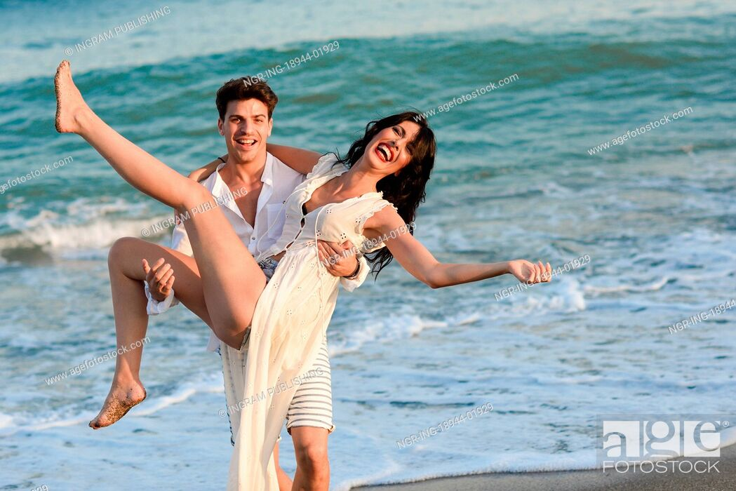 Stock Photo: Young happy couple walking in a beautiful beach. Funny Man carrying a woman on his arms. People wearing casual clothes.