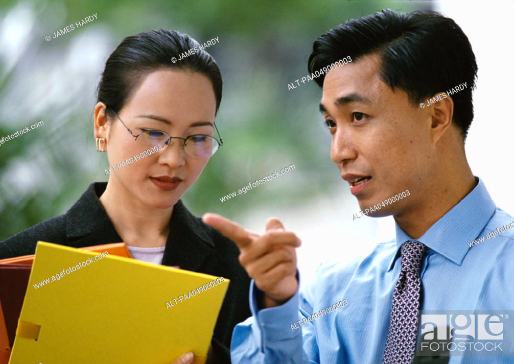 Stock Photo: Man and woman side by side, woman holding folders, head and shoulders.