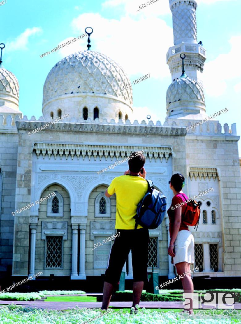 Stock Photo: Western tourists at Jumeirah Mosque in Dubai, United Arab Emirates.