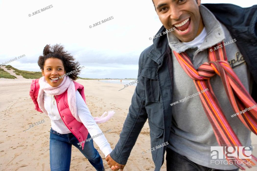 Stock Photo: Young couple hand in hand on beach, smiling, portrait.
