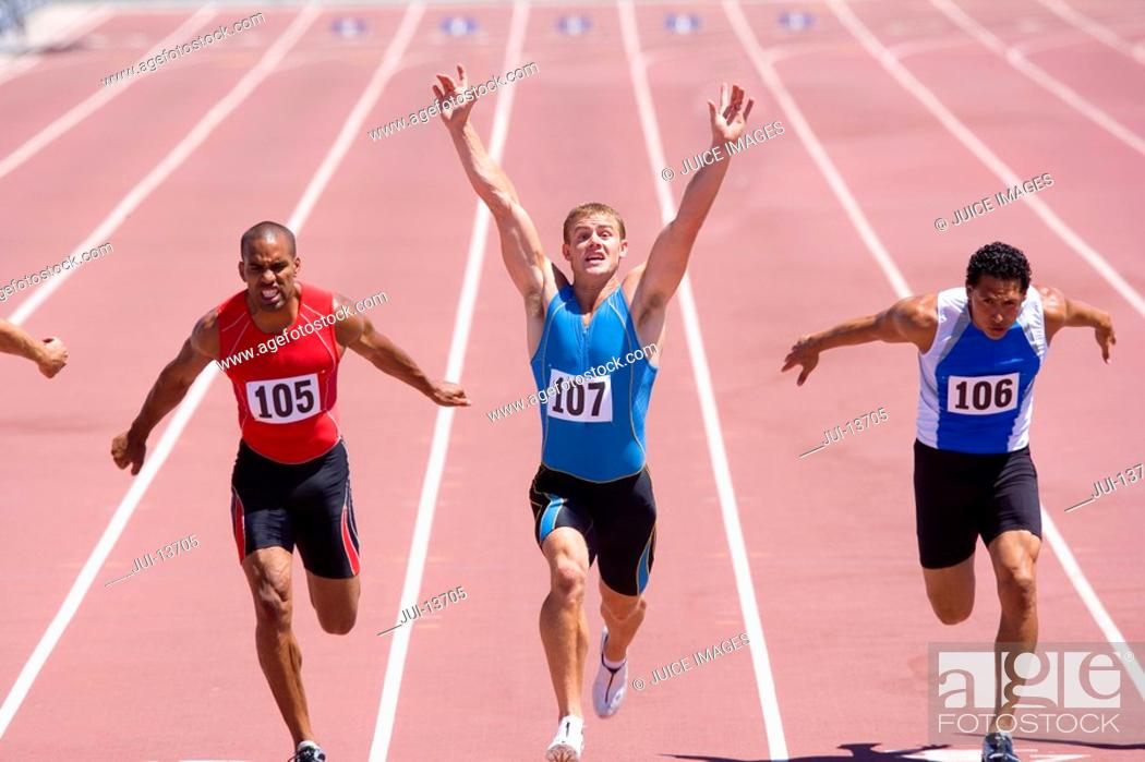 Stock Photo: Male sprinters on track, man with arms raised, elevated view.