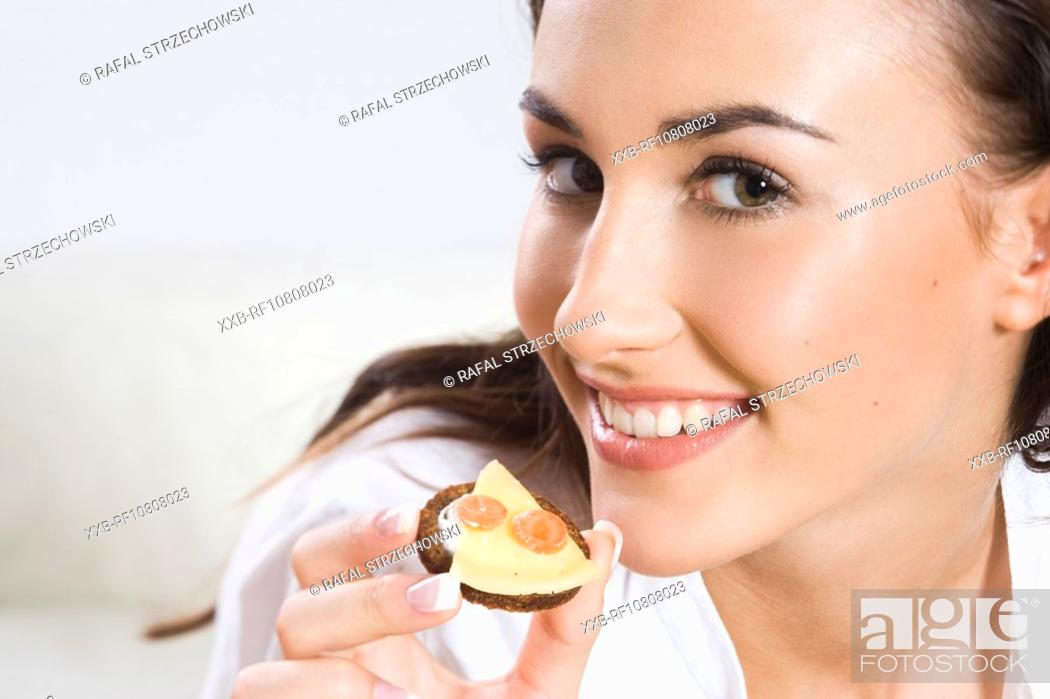 Stock Photo: Young woman eating sandwich with cheese.