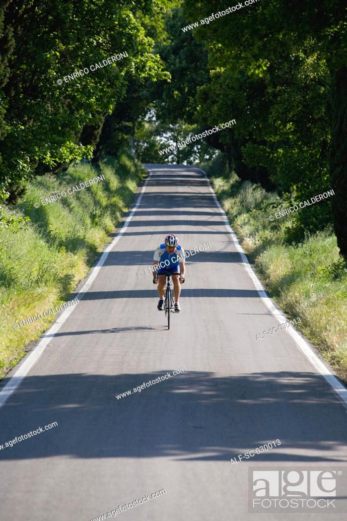 Stock Photo: Cyclist riding bicycle on deserted road, front view.