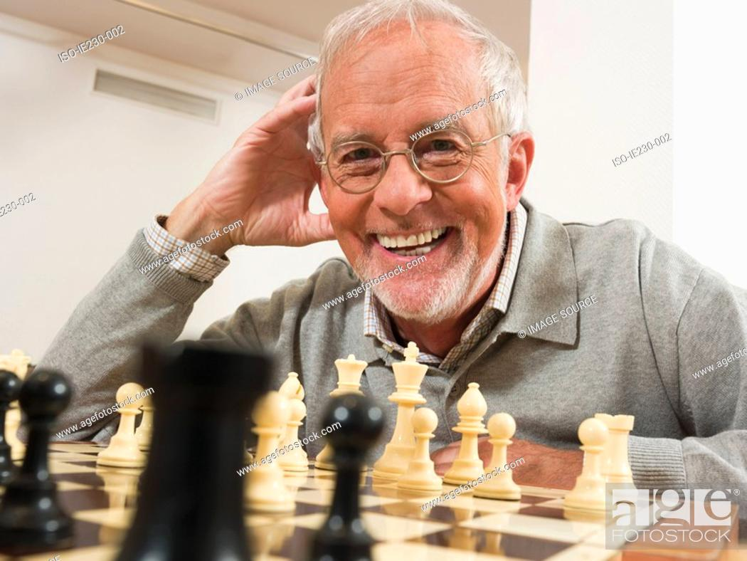 Stock Photo: Senior man playing chess.