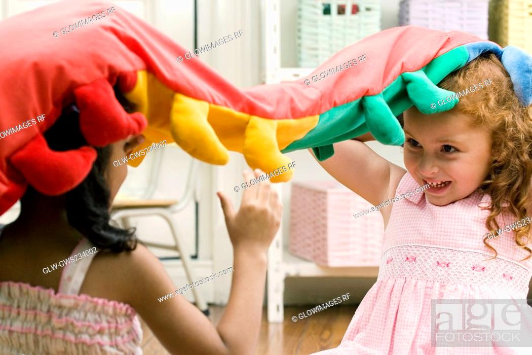 Stock Photo: Two girls playing with a stuffed toy.