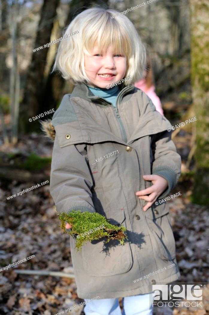 Stock Photo: Five year old girl showing a piece of moss she has found on a nature walk.