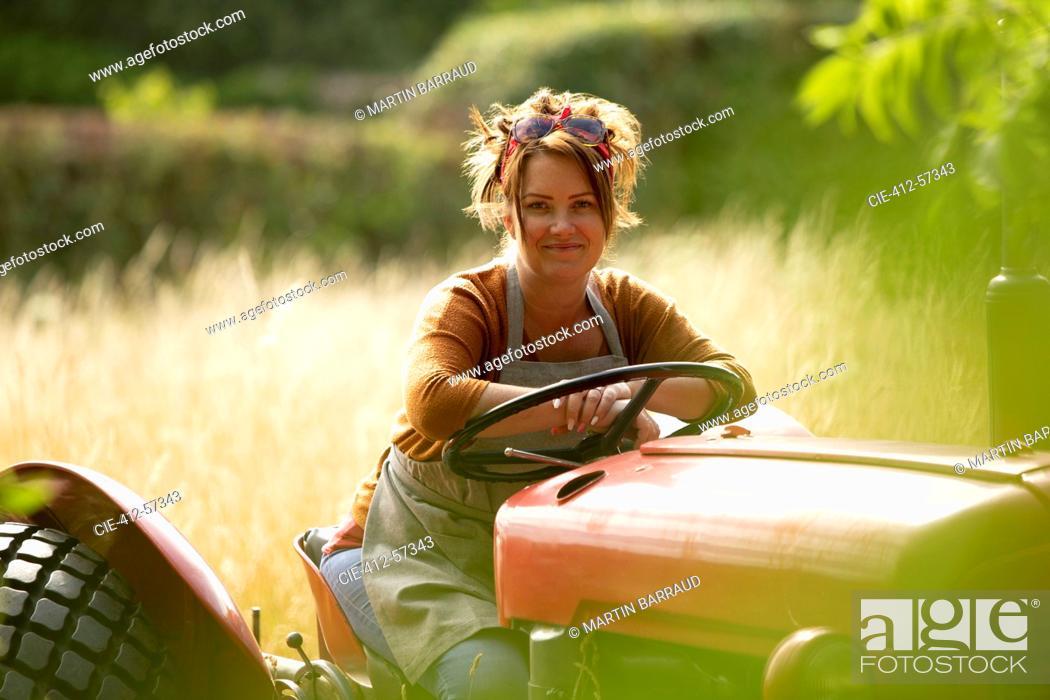 Photo de stock: Portrait happy female farmer driving tractor.