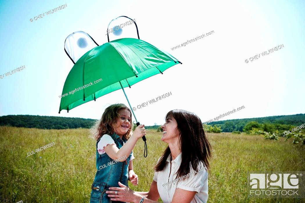 Stock Photo: Woman and girl playing with umbrella.