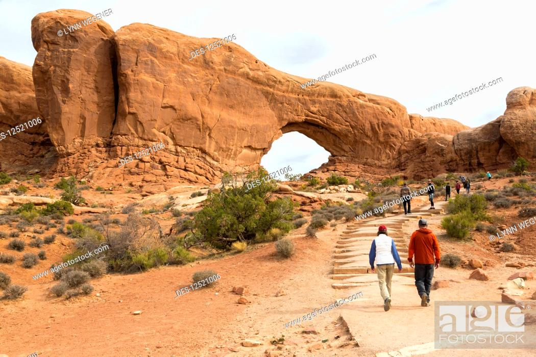 Imagen: Two hikers approaching Window Arch, Arches National Park, Utah, United States of America.