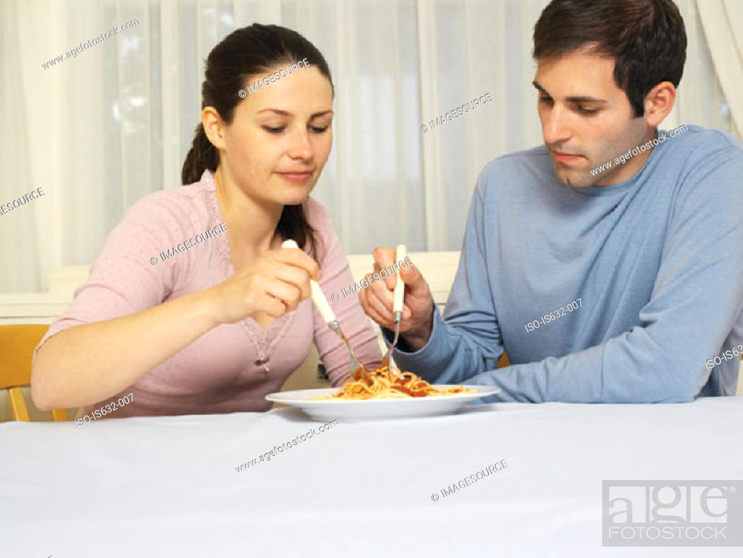 Stock Photo: Couple sharing spaghetti bolognese.