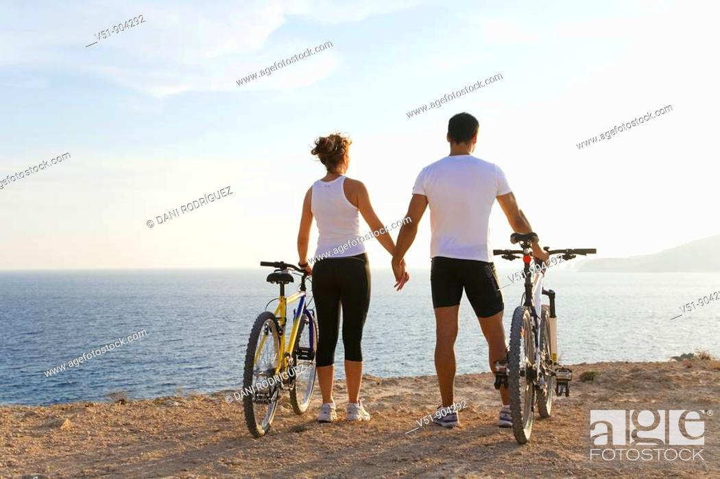 Stock Photo: Couple enjoying the views in a cliff with their bikes.