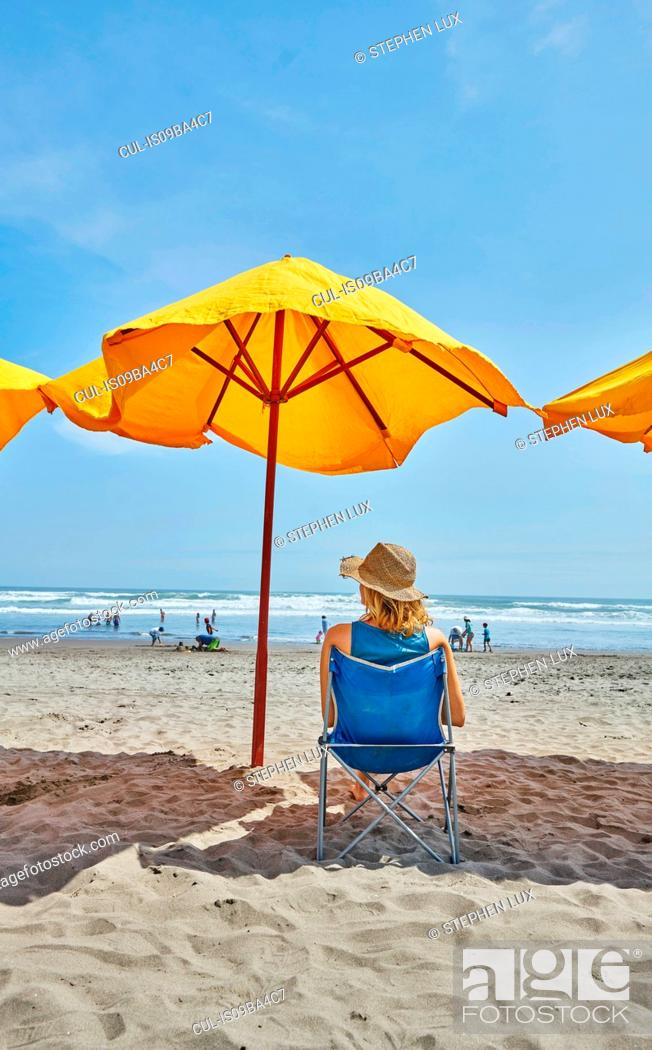 Stock Photo: Rear view of female tourist sitting under beach umbrella, Camana, Arequipa, Peru.
