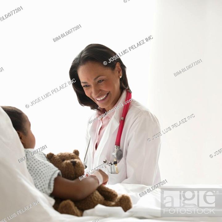 Stock Photo: Doctor examining girl in hospital bed.