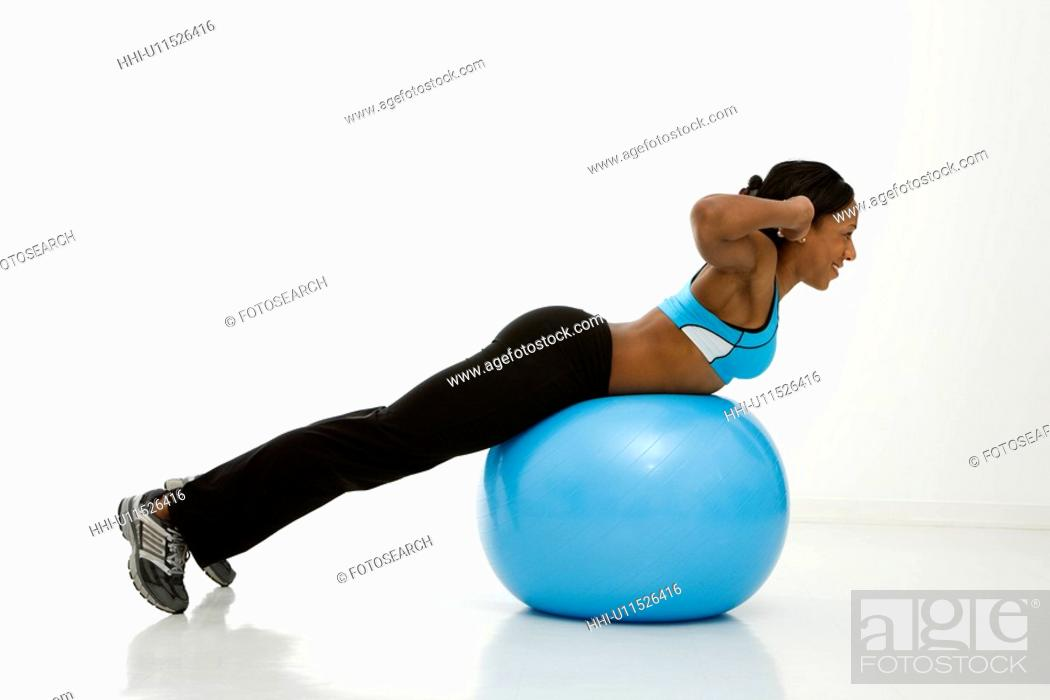 Stock Photo: Profile of African American young adult woman working out with exercise ball.