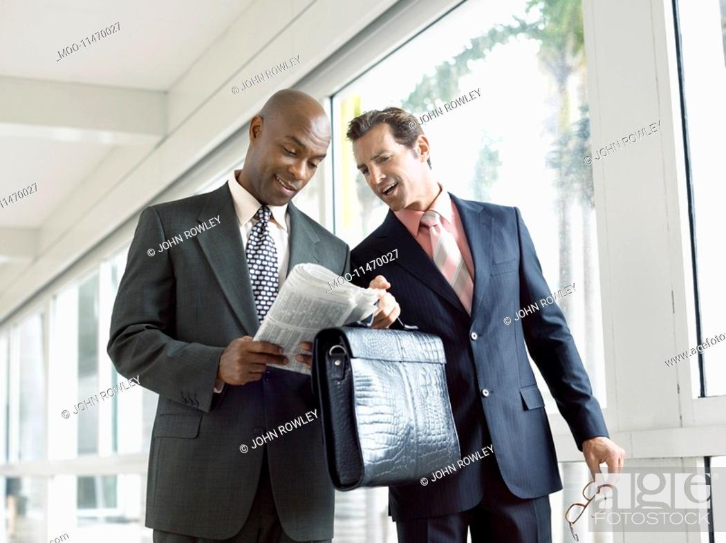 Stock Photo: Two businessmen discussing financial pages in modern hallway.
