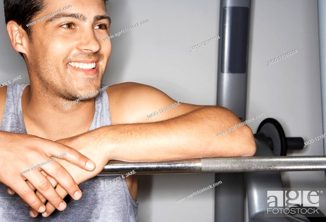 Stock Photo: Sweaty man resting on barbell after workout.