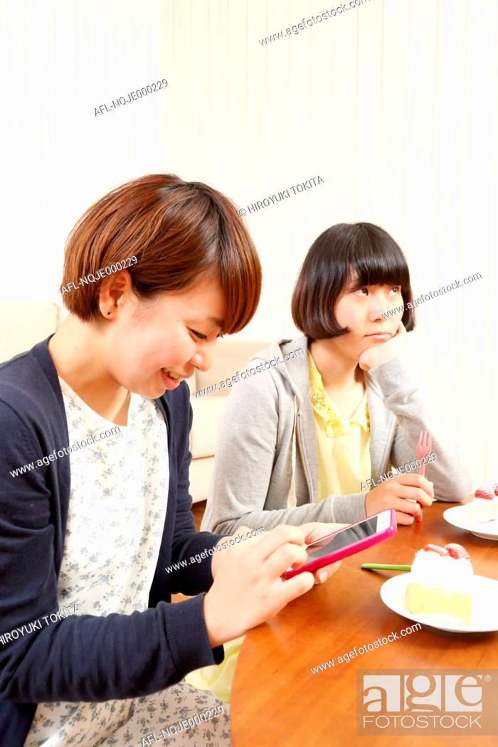 Stock Photo: Young Japanese girls having a piece of cake together in the living room.