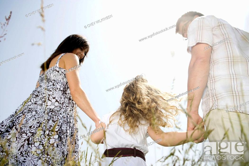 Stock Photo: Family holding hands, rear view.