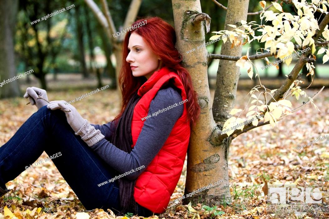 Stock Photo: A young woman leaning against a tree, thinking.