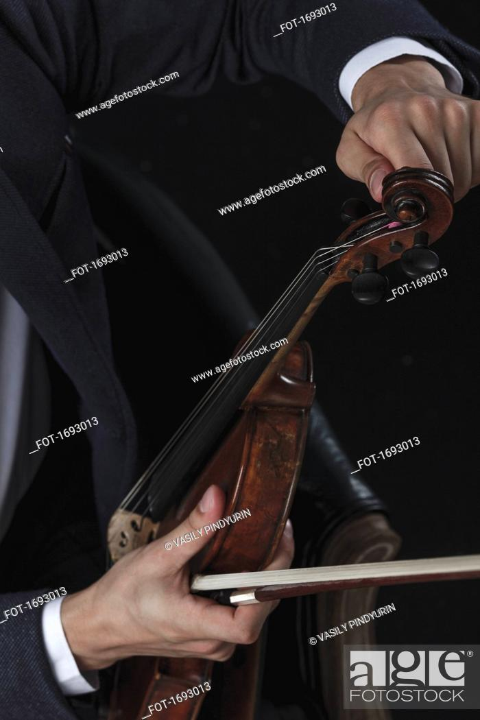 Stock Photo: Cropped image of violinist tuning violin while sitting on chair.