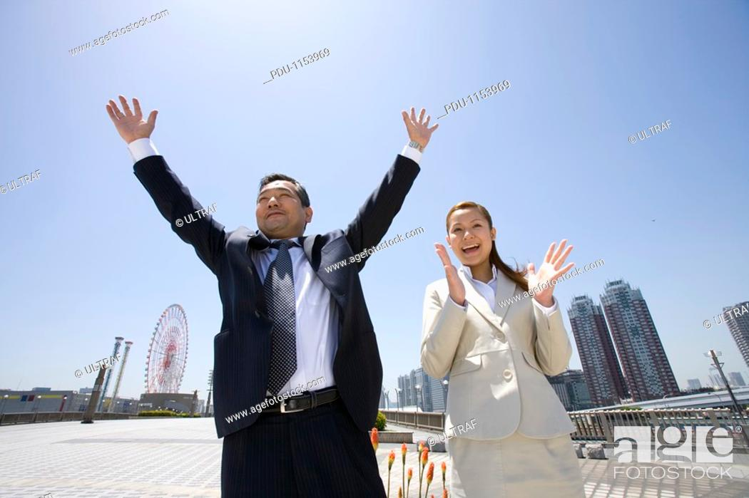 Stock Photo: Businessman and businesswoman standing in center of city.