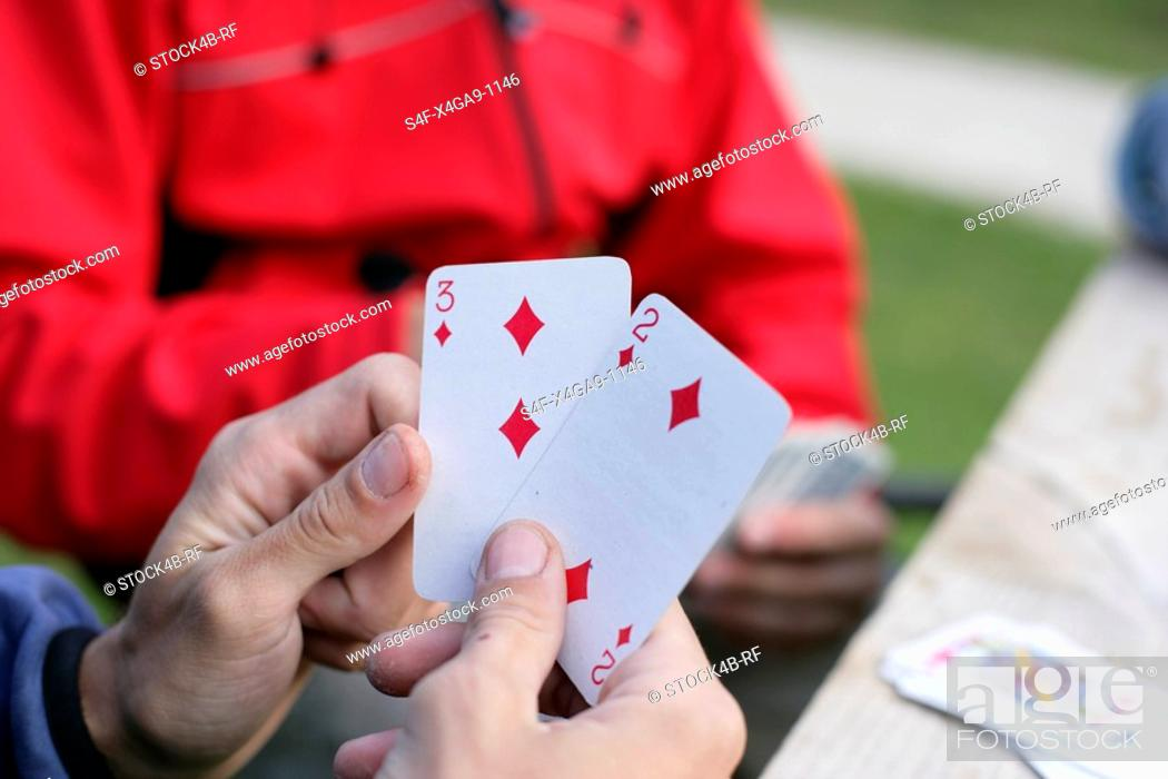 Stock Photo: Hands holding two play cards.
