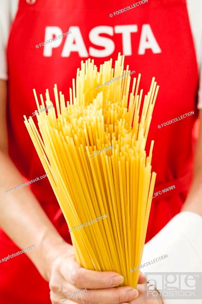 Stock Photo: Spaghetti, person with 'pasta' apron in background.