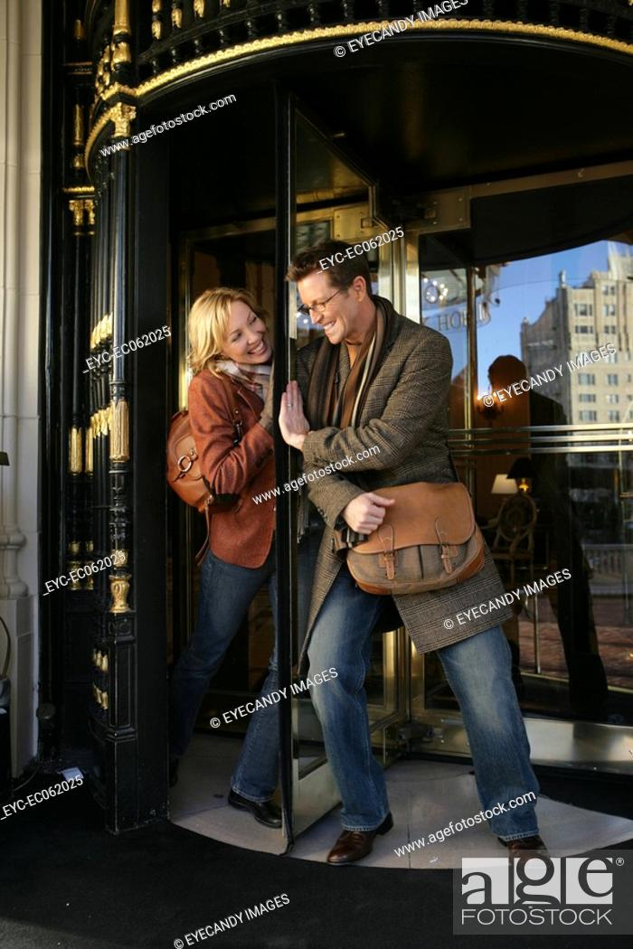 Stock Photo: Mature couple playing with revolving doors.
