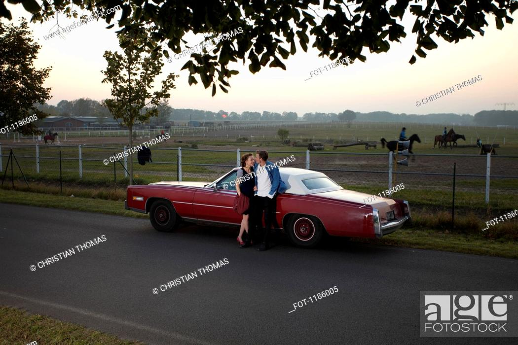 Stock Photo: A rockabilly couple leaning against a vintage car in the country.