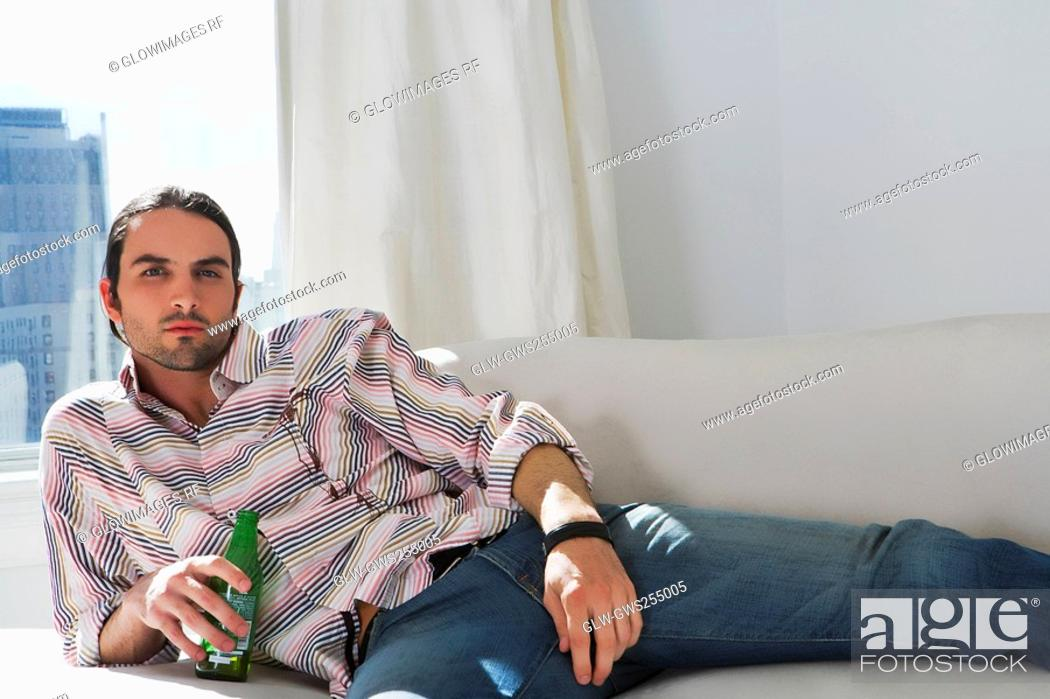 Stock Photo: Portrait of a young man lying on a couch and holding a beer bottle.