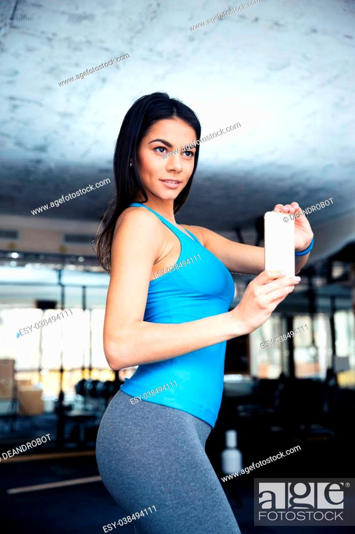 Stock Photo: Happy fit woman making selfie photo at gym.