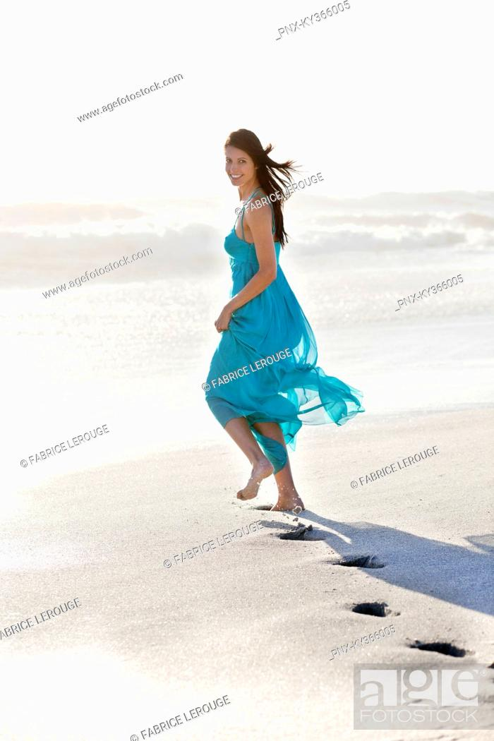 Stock Photo: Young woman's footprint while running on a beach.