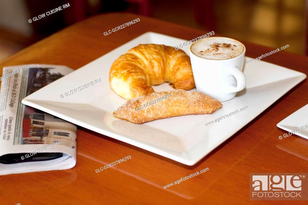 Imagen: High angle view of a croissant and sugar cracker with a cup of coffee.