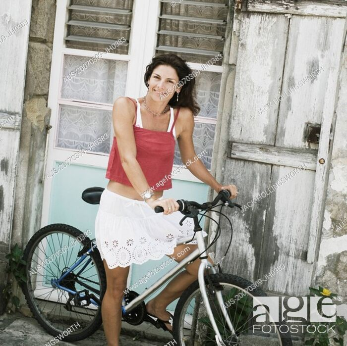 Stock Photo: Portrait of a mid adult woman riding a bicycle and smiling.