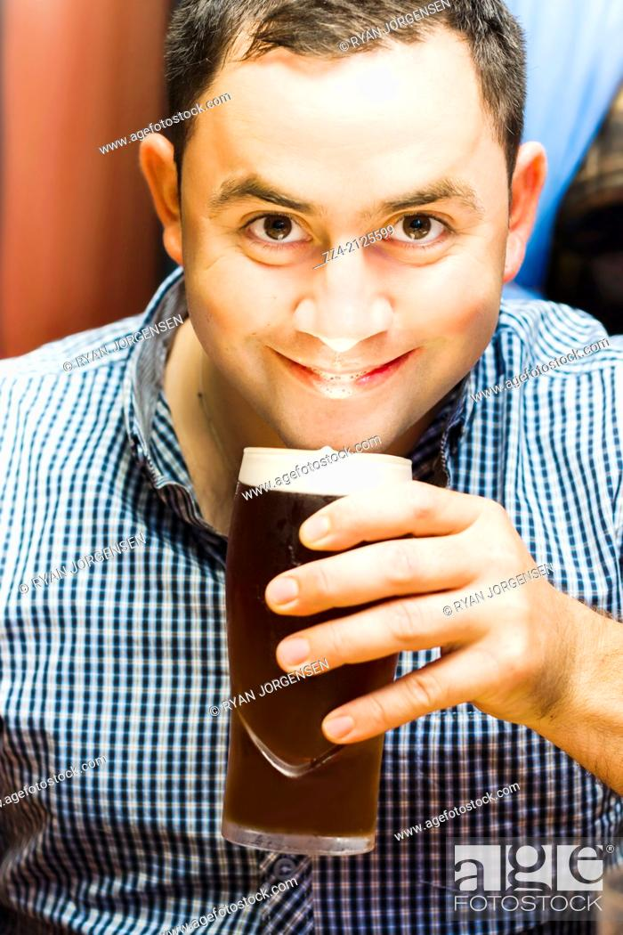 Stock Photo: Funny lifestyle photograph of a happy European English man holding and drinking pint of beer with foam head at bar location. Ale drinker.