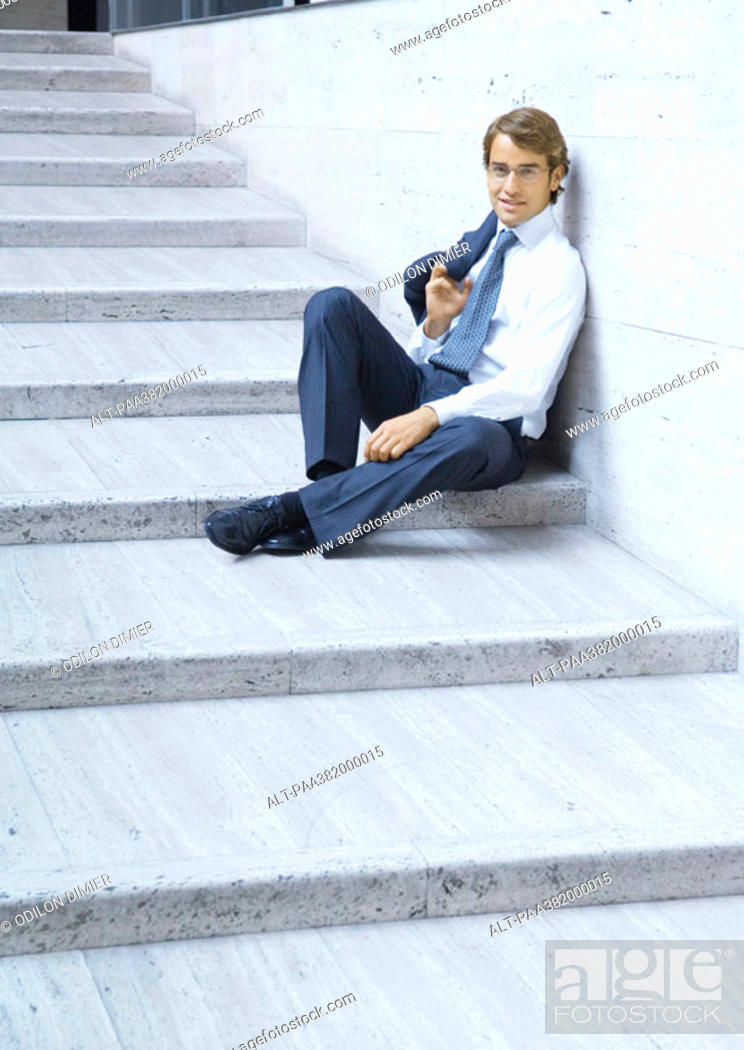 Stock Photo: Businessman sitting on steps, smiling.