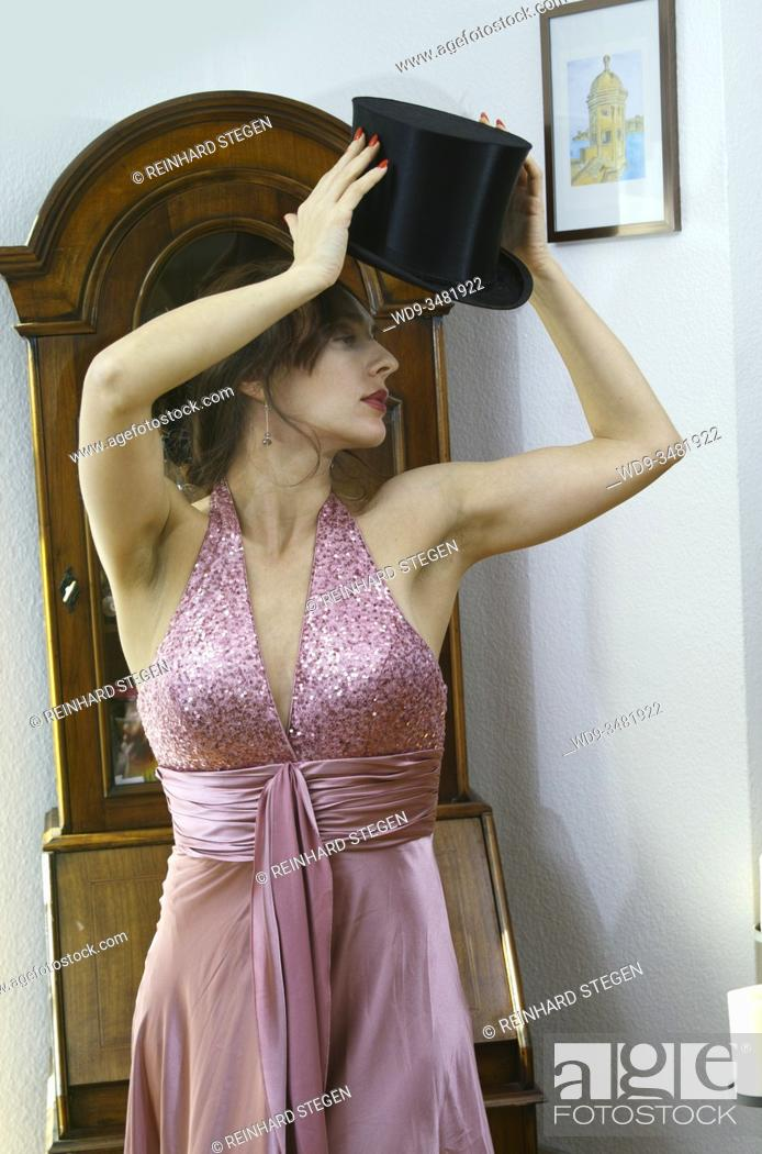 Imagen: young woman, setting up, adjusting top hat, in front of wardrobe, dressed up in 1920s style.